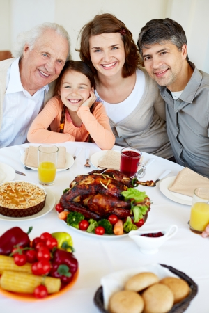 home baked: Portrait of happy family sitting at festive table and looking at camera Stock Photo