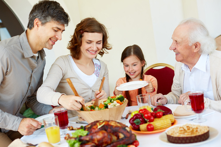 Portrait of happy family sitting at festive table while having Thanksgiving dinner photo