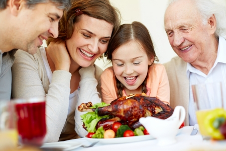 Portrait of happy family sitting at festive table and looking at roasted turkey photo
