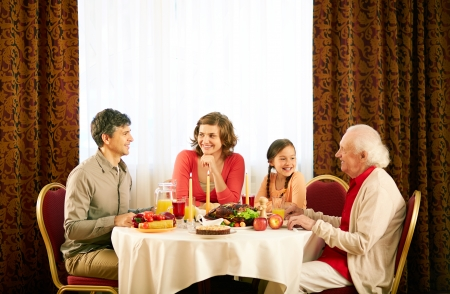 christian candle: Portrait of happy family sitting at festive table and having Thanksgiving dinner