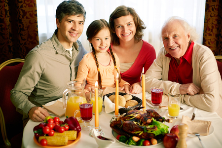 thanksgiving dinner: Portrait of happy family looking at camera on holiday evening  Stock Photo