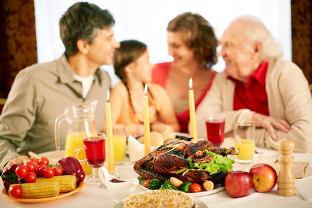 Image of festive table with family on background photo