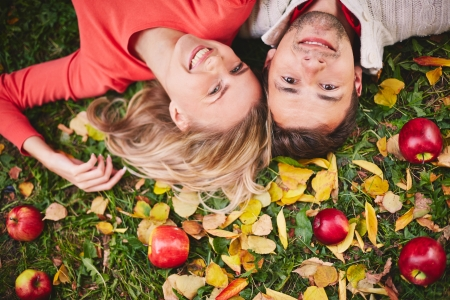 Happy young couple with ripe apples looking at camera while lying on grass photo