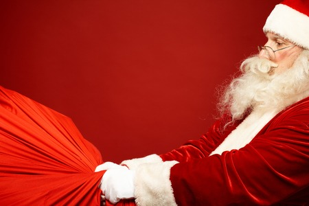 Portrait of Santa Claus carrying huge red sack with presents photo