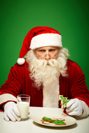 Photo of Santa Claus in eyeglasses eating gingerbread and drinking milk