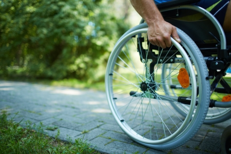 people with disabilities: Close-up of male hand on wheel of wheelchair during walk in park