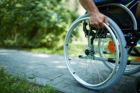 personen: Close-up van mannelijke hand op een wiel van rolstoel tijdens wandeling in het park Stockfoto