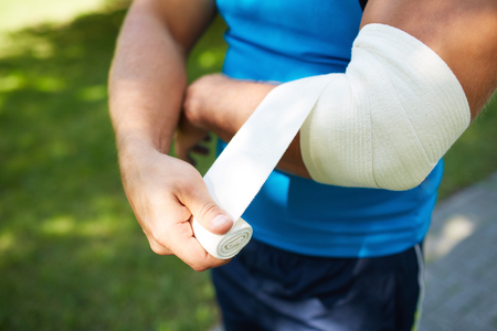 contusion: Close-up of male bandaging his arm Stock Photo