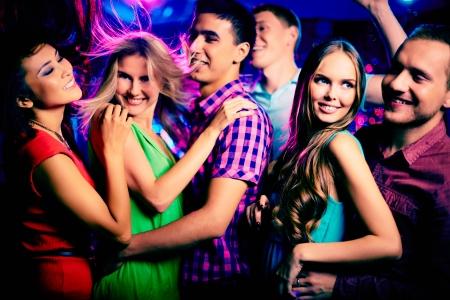 chicas bailando: Amigos felices j�venes bailando en la discoteca Foto de archivo