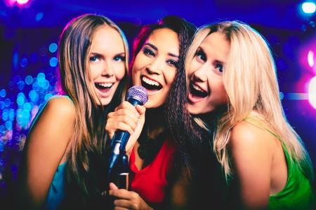 Portret van gelukkige meisjes zingen in de microfoon in de karaokebar Stockfoto