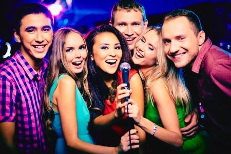 cantando: Retrato de las ni�as felices y chicos cantando en el micr�fono en el bar karaoke Foto de archivo