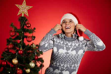 starlike: Portrait of happy girl holding star-like firtree decorations by her ears near decorated xmas tree