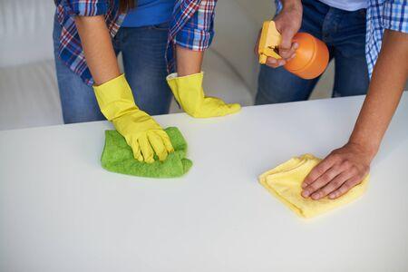 utiles de aseo personal: Primer plano de las manos femeninas y masculinas de limpieza superficie de la mesa con franelas y detergentes