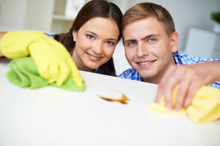 dusting: Young couple looking at camera while dusting table
