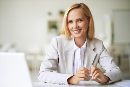 Jonge zakenvrouw op zoek naar camera met een brede glimlach Stockfoto