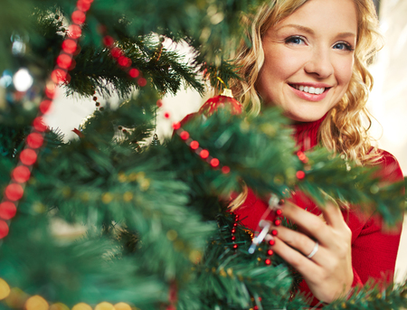 Pretty female looking at camera out of decorated firtree Stock Photo - 22709041