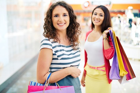 Gorgeous female with paperbags looking at camera with her friend  Stock Photo - 22726770