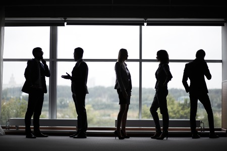 Several colleagues communicating at meeting against window photo