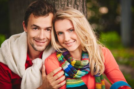 Happy young couple looking at camera outdoors photo