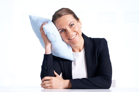 Portrait of smiling businesswoman with pillow looking at camera in isolation
