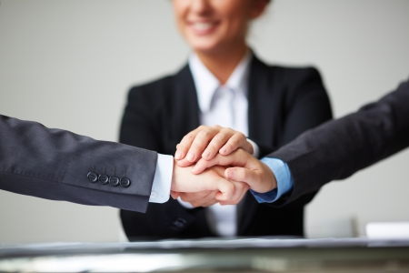 consensus: Image of pile of hands of business partners on background of businesswoman