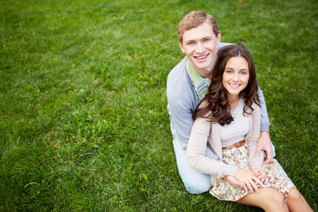 Happy girl and her boyfriend looking at camera in park photo