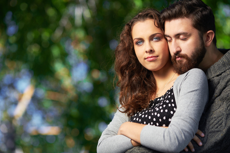 inlove: Image of affectionate man embracing his girlfriend while she looking at camera outdoors