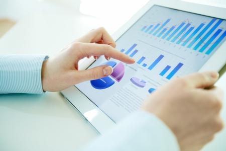 Close-up beeld van een kantoor werknemer met behulp van een touchpad om statistische gegevens te analyseren Stockfoto