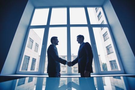 trust people: Photo of successful businessmen handshaking after striking deal
