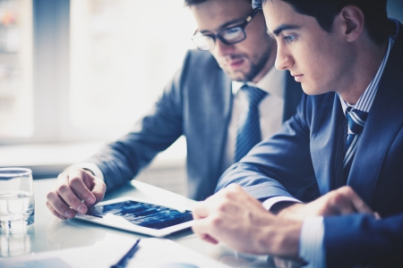 strategy meeting: Image of two young businessmen using touchpad Stock Photo