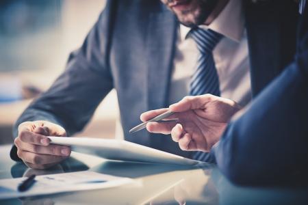 Beeld van twee jonge ondernemers met behulp van touchpad op vergadering