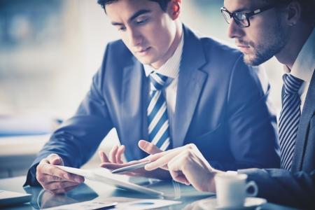 revisando documentos: Imagen de dos hombres de negocios jóvenes discutiendo el documento en el touchpad a satisfacer