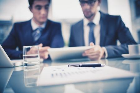 revisando documentos: Imagen de los objetos de negocio en el fondo de dos empresarios j�venes discutiendo el documento en el touchpad a satisfacer Foto de archivo