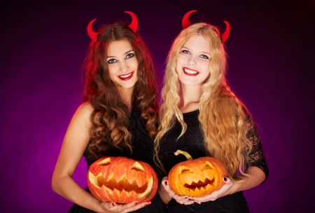 antichrist: Portrait of two horned females with carved Halloween pumpkins looking at camera Stock Photo