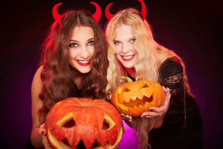 antichrist: Portrait of two horned females showing carved Halloween pumpkins and looking at camera