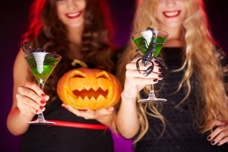 antichrist: Photo of carved Halloween pumpkin and cocktails with scorpions held by females