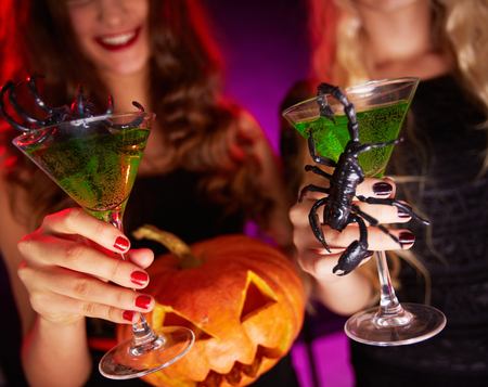 feminine background: Photo of carved Halloween pumpkin and cocktails with scorpions held by females