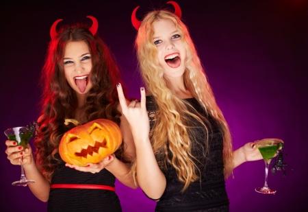 Foto van twee jonge vrouwen met Halloween pompoen en cocktails met schorpioenen plezier