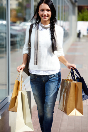 Image of happy female with paperbags walking down street photo