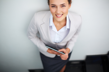 Image of smart businesswoman looking at camera over white background
