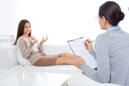 psychiatry: Upset patient describing her problem to psychiatrist in clinic Stock Photo