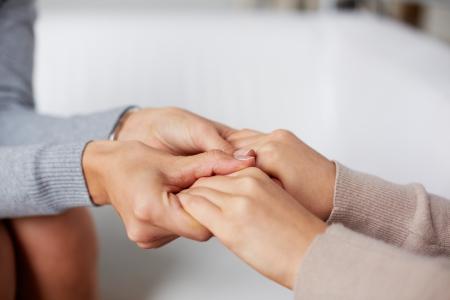 Close-up di mani psichiatra che tengono quelli del suo paziente