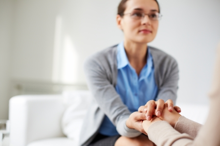 Image of psychiatrist holding hands of her patient Stock Photo