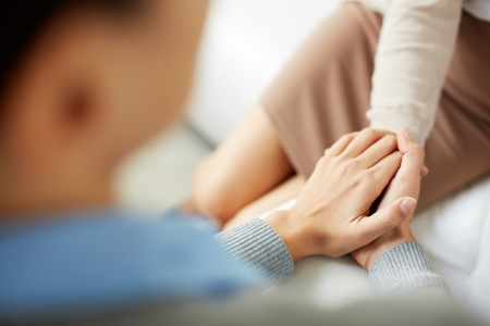 compassion: Close-up of psychiatrist keeping her hands together while listening to her patient Stock Photo