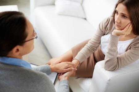 Afbeelding van de psychiater die handen van haar patiënt tijdens de bespreking van problemen Stockfoto