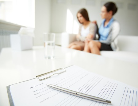 counseling session: Image of medical card with pen on background of psychiatrist comforting her patient Stock Photo