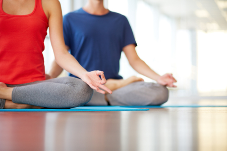 yoga man: Lower part of slim female and man on background meditating in pose of lotus in gym
