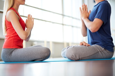 Image of young woman and man doing yoga exercise in gym photo