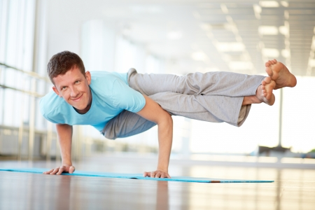 Portrait of young man doing physical exercise in gym photo