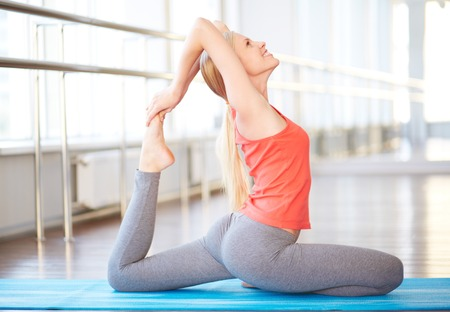 activewear: Portrait of happy young woman doing stretching exercise in gym Stock Photo